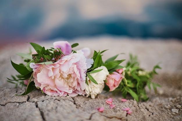 Piękny letni bukiet róż leży na popękanej ziemi