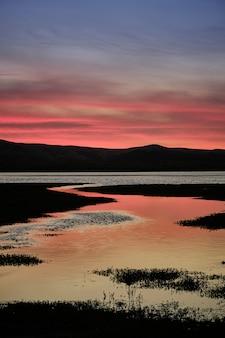 Piękny letni zachód słońca nad brzegiem jeziora z niebem o wielu kolorach i odbiciach w wodzie. długa ekspozycja