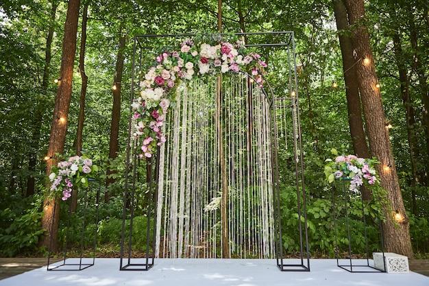 Piękny łuk ślubny na uroczystość w stylu rustykalnym położony w lesie