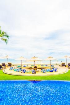Piękny luksusowy basen z parasolem i krzesło w hotelu resort