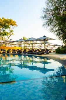 Piękny luksusowy parasol i krzesło wokół odkrytego basenu w hotelu i kurorcie z niebieskim niebem