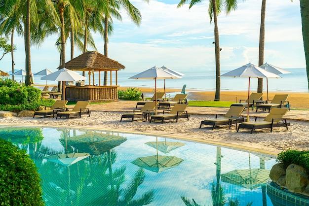 Piękny luksusowy parasol i krzesło wokół odkrytego basenu w hotelu i ośrodku z palmą kokosową na niebie o zachodzie słońca lub wschodzie słońca. koncepcja wakacji i wakacji