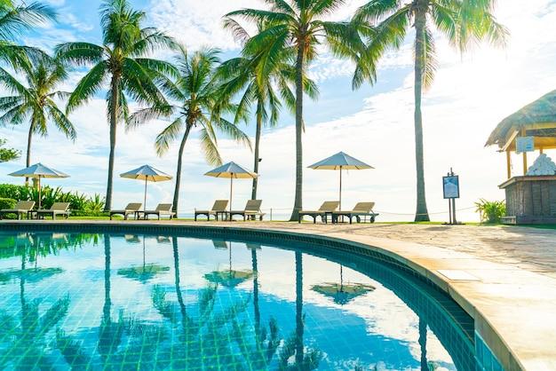 Piękny luksusowy parasol i krzesło wokół odkrytego basenu w hotelu i ośrodku z palmą kokosową na niebie o zachodzie słońca lub wschodzie słońca