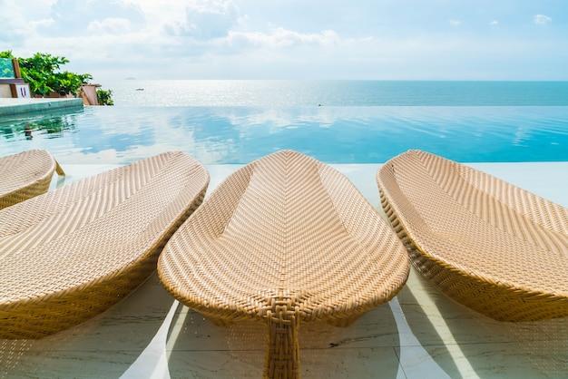 Piękny luksusowy parasol i krzesło wokół odkrytego basenu w hotelu i ośrodku