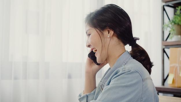 Piękny mądrze azjatycki młody przedsiębiorca biznesowej kobiety właściciel sme używa smartphone online wezwanie