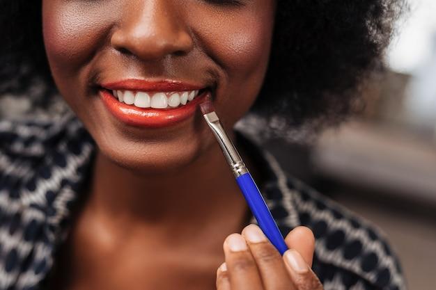 Piękny makijaż. niesamowita kobieta z kręconymi włosami uśmiecha się, ciesząc się procesem makijażu