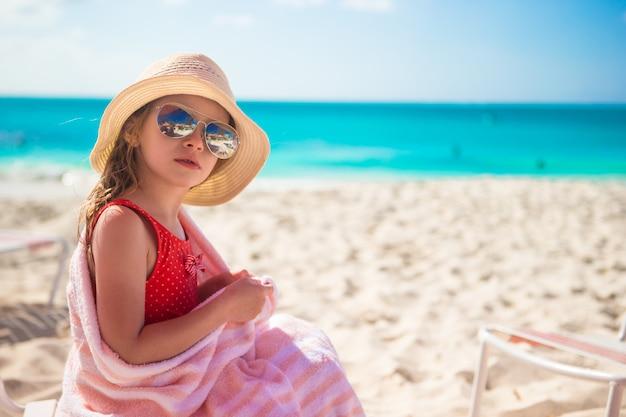Piękny małej dziewczynki obsiadanie na krześle przy plażą podczas wakacje