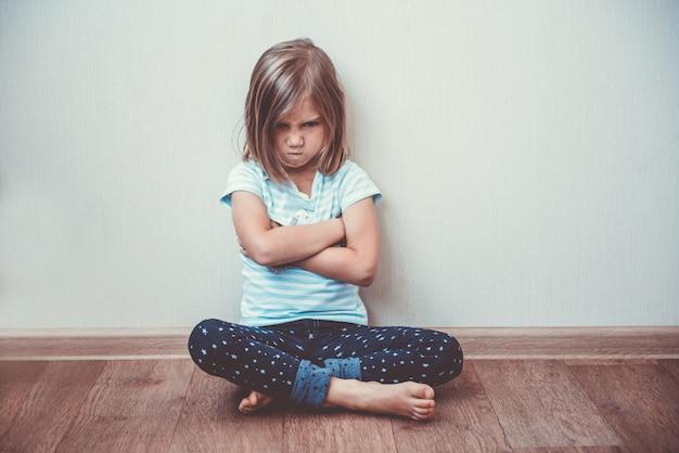 Piękny małej dziewczynki obsiadanie na podłoga, stonowany wizerunek. rozczarowanie, smutek, melancholia