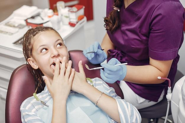 Piękny małej dziewczynki obsiadanie w dentysty biurze