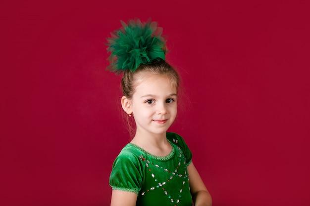 Piękny małej dziewczynki princess tanczy w luksus zieleni sukni odizolowywającej na czerwieni ścianie. karnawałowa impreza z kostiumami