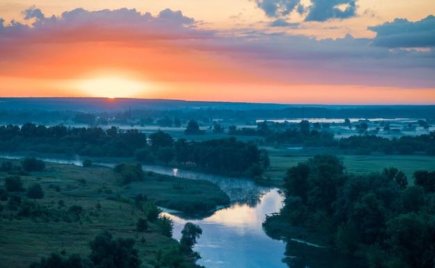 Piękny, malowniczy krajobraz rzeki z czystą, cichą wodą między zielonymi polami i lasami w letni wieczór