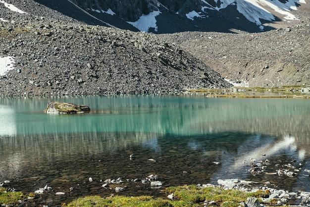 Piękny malowniczy krajobraz z turkusowym górskim jeziorem z przejrzystą wodą i kamienistym dnem. lazurowe jezioro polodowcowe z czystą powierzchnią wody w słońcu. biały śnieg i zielona trawa w pobliżu górskiego jeziora.