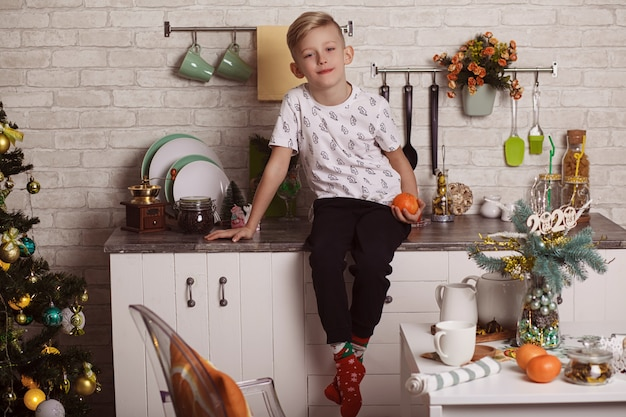 Piękny mały blond chłopiec siedzi na kuchennym stole i trzyma w ręku pomarańczę