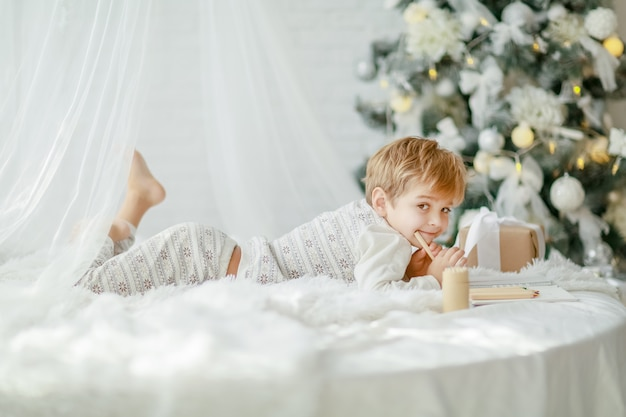 Piękny mały chłopczyk w piżamie z gwiazdami świętuje boże narodzenie.