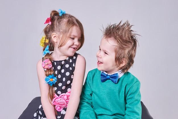 Piękny mały chłopiec i dziewczynka szczęśliwie uśmiechający się i patrzący na siebie