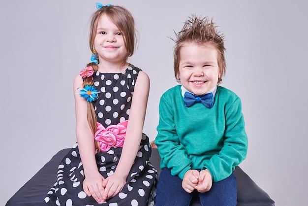 Piękny mały chłopiec i dziewczynka uśmiechający się z zabawnymi wyrazami twarzy