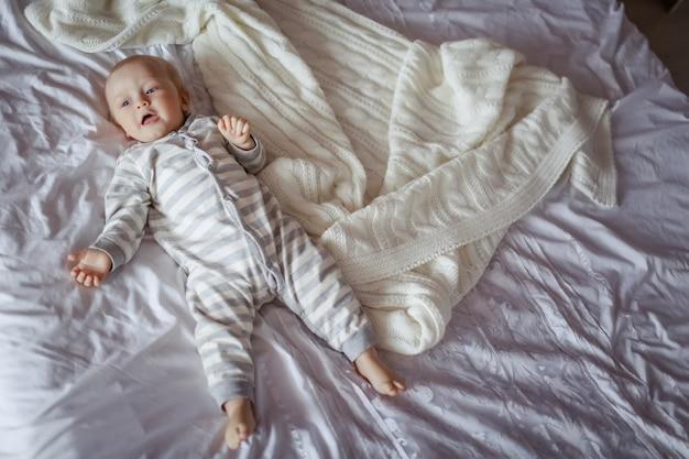 Piękny mały chłopiec lying on the beach na białym prześcieradle na łóżku