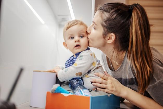 Piękny mały chłopiec siedzi w pudełku na blacie kuchennym i gra, podczas gdy jego matka go całuje.