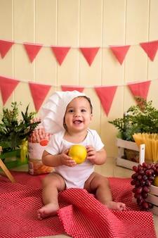 Piękny mały chłopiec w białym kapeluszu szefa kuchni trzyma gruszkę