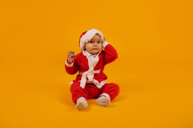 Piękny mały chłopiec w stroju świętego mikołaja i czapce mikołaja na nowy rok