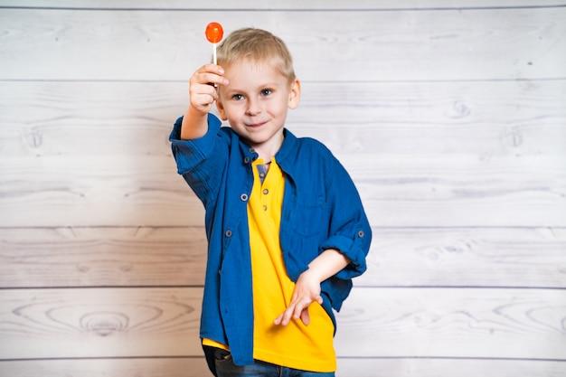Piękny mały chłopiec z lizakiem w rękach