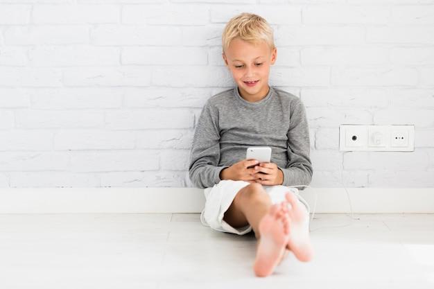 Piękny mały chłopiec za pomocą jego smartphone