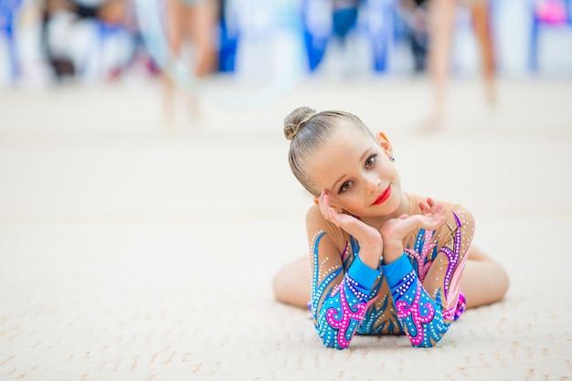 Piękny mały gimnastyk trenujący na dywanie i gotowy do zawodów