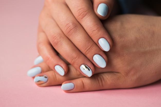 Piękny manicure. lakier hybrydowy w kolorze niebieskim, tłoczony.