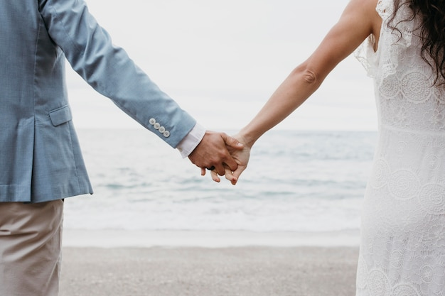 Piękny mąż i żona pozują na plaży na weselu