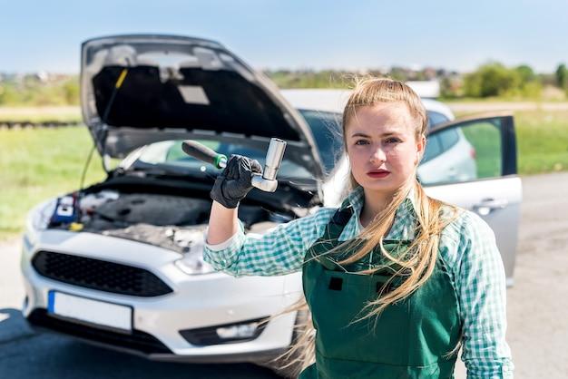 Piękny mechanik w pobliżu samochodu z różnymi narzędziami