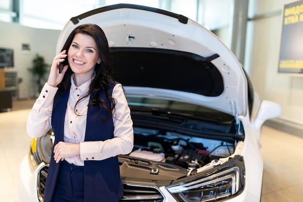 Piękny menedżer sprzedaży sprawdza nowy samochód i rozmawia przez telefon w salonie dealerskim