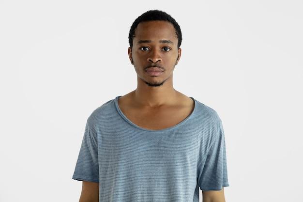 Piękny męski portret w połowie długości na białym tle na białej ścianie. młody emocjonalny afroamerykanin w niebieskiej koszuli. wyraz twarzy, ludzkie emocje, koncepcja reklamy. stojąc, patrząc.