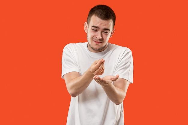 Piękny męski portret w połowie długości na białym tle na pomarańczowym tle. młody emocjonalnie zaskoczony mężczyzna