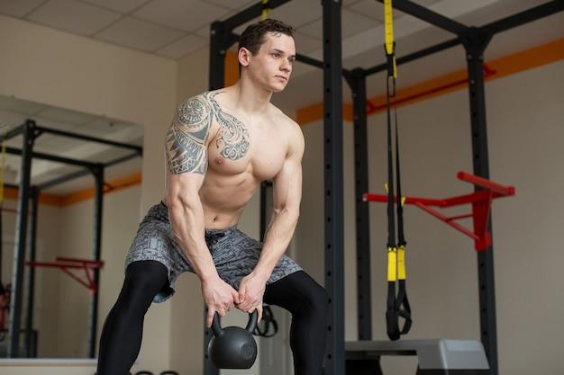 Piękny mężczyzna kuca z kettlebell na siłowni