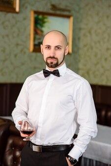 Piękny mężczyzna pije koniak w restauracji