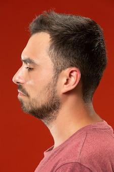 Piękny mężczyzna szuka zaskoczony i zdezorientowany na białym tle na czerwono