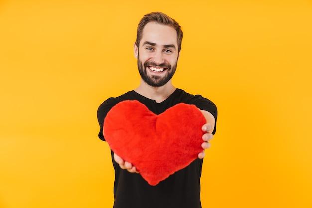 Piękny mężczyzna ubrany w podstawową czarną koszulkę uśmiechający się i trzymający czerwone papierowe serce na białym tle nad żółtą ścianą