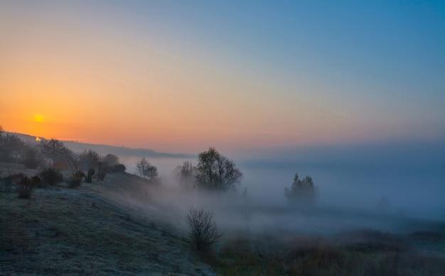 Piękny mglisty jesienny wschód słońca krajobraz.