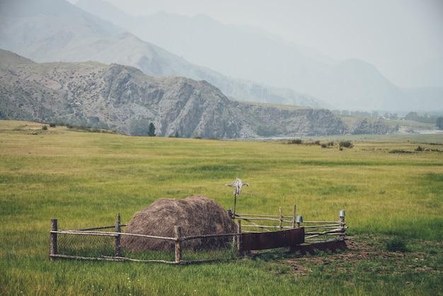 Piękny mglisty krajobraz górski z strachem na wróble na drewnianym płocie wokół stogu siana na tle gór i skał sylwetki we mgle. stos siana jest otoczony drewnianym płotem w odcieniach vintage.