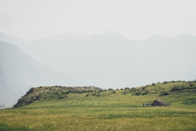 Piękny mglisty krajobraz górski z strachem na wróble na drewnianym płocie wokół stogu siana w pobliżu wzgórz na tle gór sylwetki we mgle. stos siana jest otoczony drewnianym płotem w odcieniach vintage.