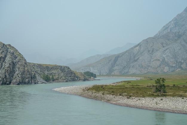 Piękny mglisty krajobraz górski z szeroką górską rzeką. ciemnozielona ponura sceneria z dużą górską rzeką we mgle. ciemny atmosferyczny widok na wielką rzekę wśród wielkich gór w deszczową pogodę.