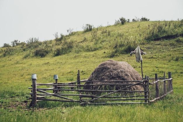 Piękny mglisty krajobraz górski ze strachem na wróble na drewnianym płocie wokół stogu siana w górach w odcieniach vintage. stos siana jest otoczony drewnianym płotem ze strachem na wróble na tle wzgórz we mgle.