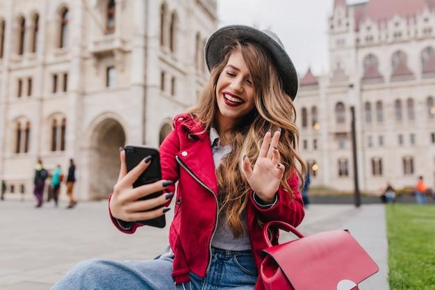 Piękny międzynarodowy studentka podejmowania selfie przed starym pięknym budynkiem