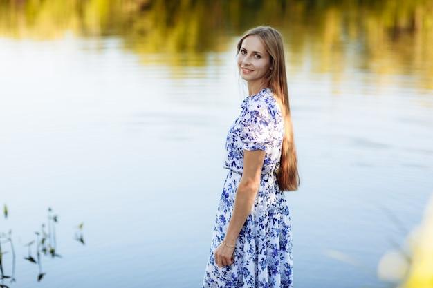 Piękny młoda kobieta portret w polu. atrakcyjna brunetka dziewczyna z długimi kręconymi włosami w białej sukni marzeń. portret pięknej dziewczyny długowłosy
