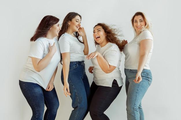 Piękny. młode kobiety rasy kaukaskiej dorywczo zabawy razem. przyjaciele pozujący na białym tle i śmiejący się, wyglądają na szczęśliwych, zadbanych. pozytywne ciało, feminizm, kochanie siebie, koncepcja piękna.