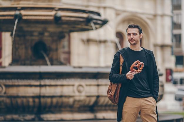Piękny młodego człowieka mienia precel i relaksować w parku