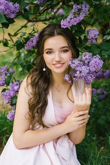 Piękny młodej dziewczyny obsiadanie na ziemi w ogródzie z kwitnącym bzem. jest szczęśliwa i uśmiecha się pięknym uśmiechem z białymi zębami. profesjonalny makijaż i czysta piękna skóra