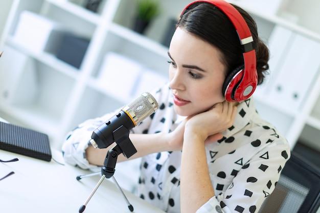 Piękny młodej dziewczyny obsiadanie w hełmofonach z mikrofonem przy stołem w biurze i opowiadać.