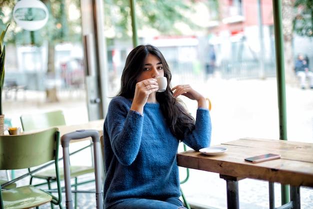 Piękny młodej kobiety obsiadanie podczas gdy pijący kawę w kawiarni