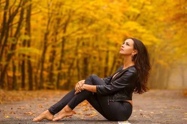 Piękny młodej kobiety obsiadanie w jesień parku na drodze w czerni.